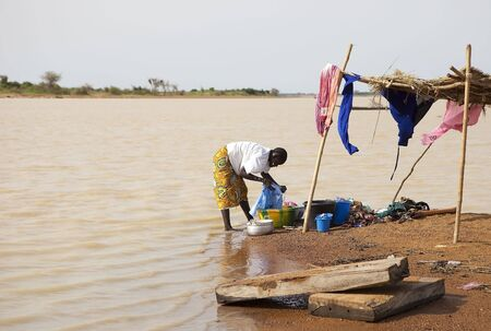 lack of water: Djenne,Mali - August 18,2009 : African woman washing in the river, the lack of running water forces women to use the river as laundry
