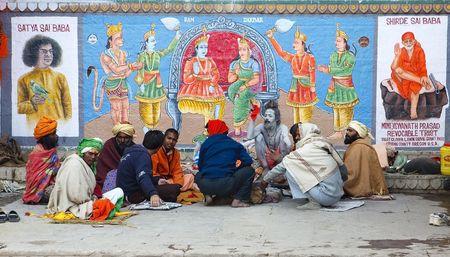 Varanasi,India - January 1,2010 : Naga Sadhu with his disciples, the Nagas covering his body with sacred ashes.