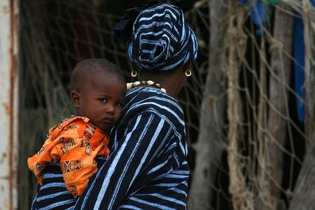 Elinkine,Casamance,Senegal - February 18,2007 : African mother carries her child back in the port of Elinkine, point of departure for boats bound for Spain.