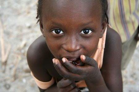 Island of Carabane,Casamance,Senegal - February 18,2007 : Girl on the island of Carabane posing while carrying food to their mouths. Stock Photo - 6886669