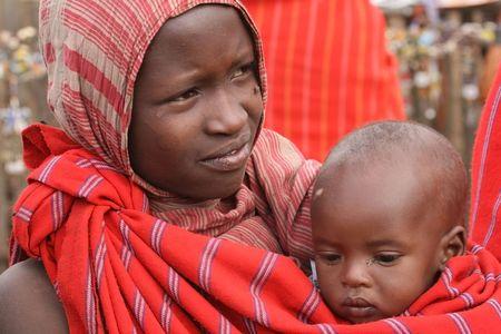 17: Ngorongoro, Tanzania - agosto 17,2007: mujer Masai con su hijo, ex de los guerreros que ahora tienden a ganado.