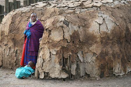 Ngorongoro, Tanzania - agosto 18,2007: mujer de Masai cuidando de sus hijos fuera de su casa, las mujeres son responsables de las labores domésticas y el cuidado de los niños en la aldea.
