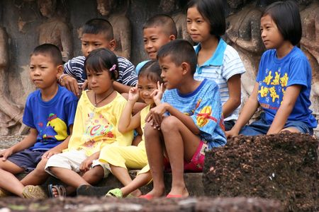 Sukhothai, Tailandia - agosto 13,2005: los niños mirar atentamente las explicaciones de su profesor, muchos niños y niñas van a templos para estudiar la historia de su país.