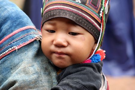 Chiang Rai,Thailand - August 15,2005 : Mother carries her baby in village Egaw, the Egaw mainly engaged in the cultivation of opium, mainly controlled by drug traffickers.