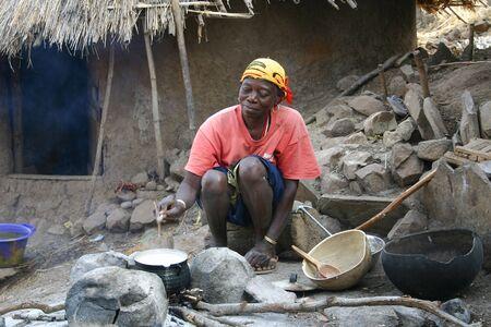 Country Bassari,Senegal - February 15,2007 :  Women Bedik preparing food, women are responsible for meeting the needs of the village.