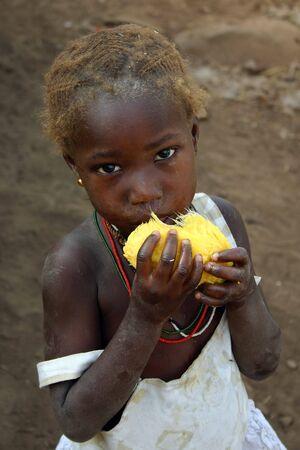 Kedougou,Country Bassari,Senegal - February 15,2007 : Bedic ethnic girl posing while eating fruit, are an ethnic minority Bedic located in the country Bassari.