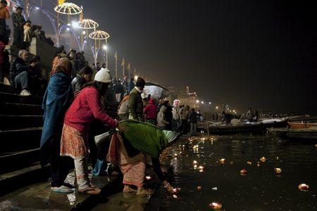 believers: Varanasi,India - December 31,2009 : Offerings to the Ganges, in the Aarti ceremony believers make offerings to the river Ganges with flowers and candles. Editorial