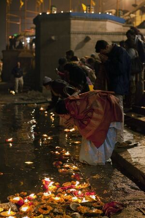 believers: Varanasi,India - December 31,2009 : Offerings to the Ganges, in the Aarti ceremony believers make offerings to the river Ganges with flowers and candles. Editorial