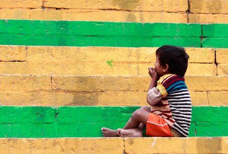 Varanasi, India - enero 2,2010: niño sentado en los pasos de un ghat proteger a la ciudad de las inundaciones del río fueron construidos de escaleras de piedra en toda la ciudad.