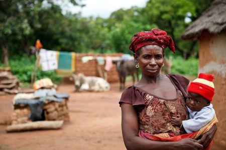 ni�os pobres: Pa�s Senoufo, Burkina Faso - agosto 13,2009: mujer Senoufo cuidado de su hijo, la tasa de mortalidad infantil en 2007 es de 8,5%.