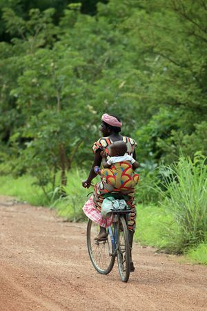 Tiebele, Burkina Faso - August 11, 2009: African Woman carrying her baby by bicycle, the bicycle is the popular Means of transport,