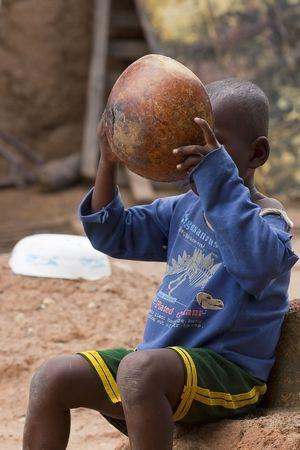 Gaoua, Burkina Faso - agosto 12.2009: niño de la étnica Lobi comer, el lobi hecha de arcilla utensilios para cocinar