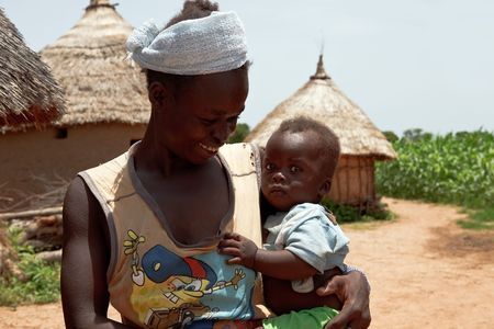 africa kiss: Country Bissa, Burkina Faso - August 9.2009: Mother caring for her child, women of ethnic Bissa care for children and working on the tasks of the village
