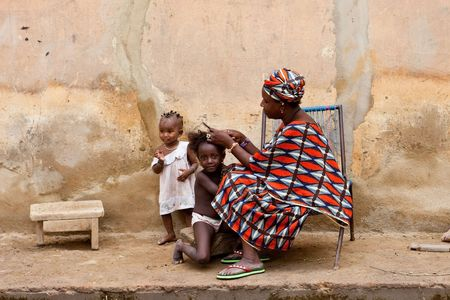 Mopti,Mali - August 16,2009 : African woman combing her daughters, usual practice in African culture. Stock Photo - 6961754