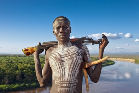 ethnic group: omo walley, ethiopia, august 13, 2011 - man of the karo ethnic group posing with his rifle.