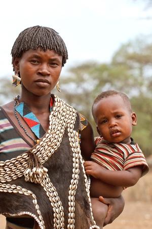 Valle de Omo, Etiopía - 10 de agosto, 2011: las mujeres de la etnia tsemay con su hijo en el pueblo, los grupos étnicos del Valle de omo podrían desaparecer con la construcción de la represa hidroeléctrica de gibe iii.