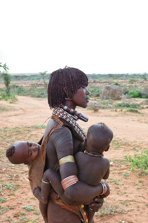 omo valley, ethiopian - august 15, 2011: women of ethnic hamer with their children in the village, the omo valley ethnic groups could disappear with the construction of gibe iii hydroelectric dam.