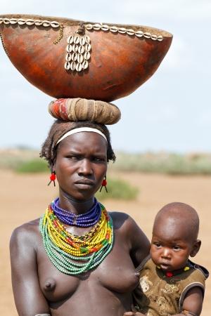 ETHIOPIË - AUG 15:?? Vrouwen van etnische Erbore met haar kind, Kan de etnische groepen in de De Omo-vallei verdwijnen als gevolg van Gibe III hydro-elektrische dam. op 15 aug 2011 in Omo Vallei, Ethiopië. Stockfoto - 14628735