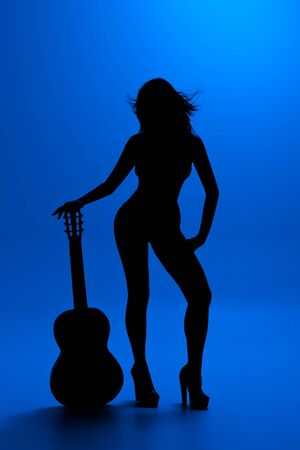 woman with guitar silhouette on blue background photo