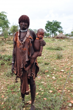 Dimeka, ethiopian - august 13, 2011: women of ethnic hamer with your child in the village, the omo valley ethnic groups could disappear with the construction of gibe iii hydroelectric dam.