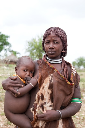 africa child: Dimeka, ethiopian - august 13, 2011: women of ethnic hamer with your child in the village, the omo valley ethnic groups could disappear with the construction of gibe iii hydroelectric dam. Editorial