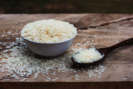 Rice with wooden spoon and white cup on wooden table  photo