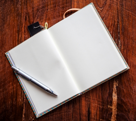 Open a blank white notebook and pen on wood background photo
