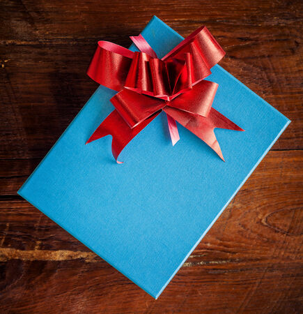 blue gift box with red ribbon on wood for vintage photo