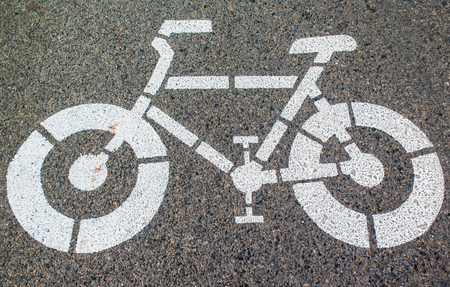 White arrows and bicycle sign path on the road Stock Photo - 25209992