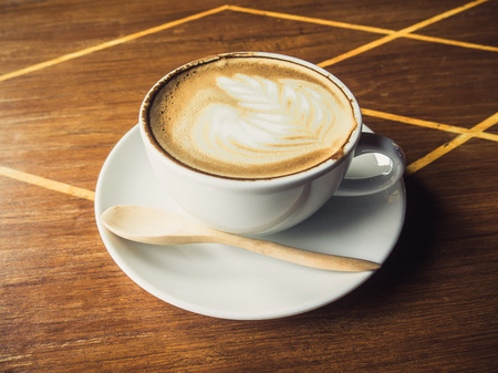 Cup of latte coffee on wooden photo