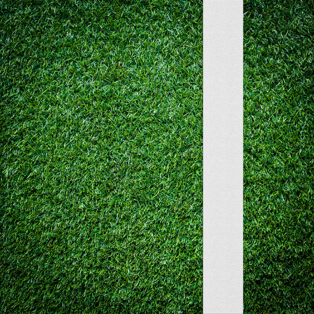 White stripe on the green soccer field from top view photo