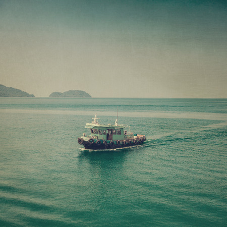 Fishing boat on blue sea vintage. photo