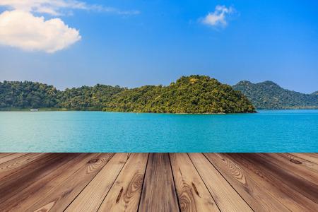 Wood floor and blue sea with island Standard-Bild