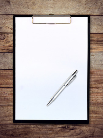 white paper clipboard on wood background with pen