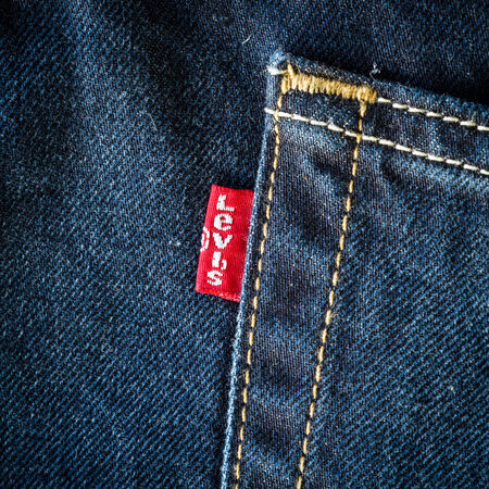 levi: CHIANG MAI, THAILAND- FEBRUARY 15, 2015: Close up of the Levis red label on the back pocket of a pair of denim jeans. Levis is a brand name of Levi Strauss and Co, founded in 1853