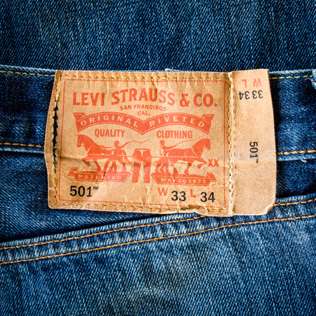 levis: CHIANG MAI, THAILAND- FEBRUARY 15, 2015 - Closeup of old leather like heavy card stock label of a pair of Levis brand of denim jeans. Levi Strauss & Co. is a worldwide clothing corporation. Editorial