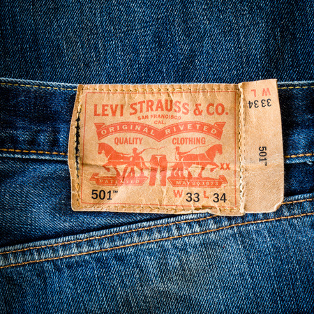 levi: CHIANG MAI, THAILAND- FEBRUARY 15, 2015 - Closeup of old leather like heavy card stock label of a pair of Levis brand of denim jeans. Levi Strauss & Co. is a worldwide clothing corporation. Editorial
