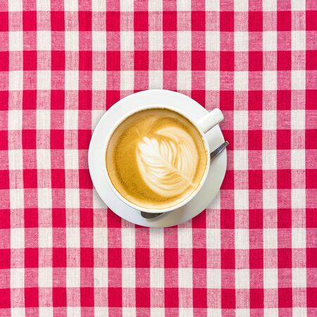 checkered background: cappuccino coffee on white and red checkered background close up
