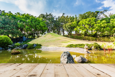 asian gardening: Wood floor on Pond and Water Landscape in Japanese Garden Stock Photo