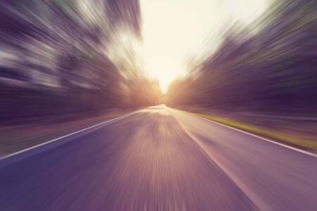 fast lane: Empty asphalt road in motion blur and sunlight with vintage tone.