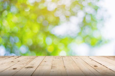 groen blad bokeh wazig en houten tafel voor natuur achtergrond
