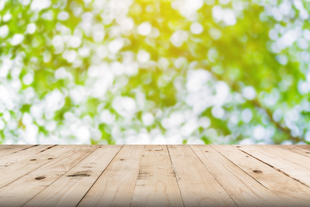 green leaf bokeh blurred and wood table for nature background