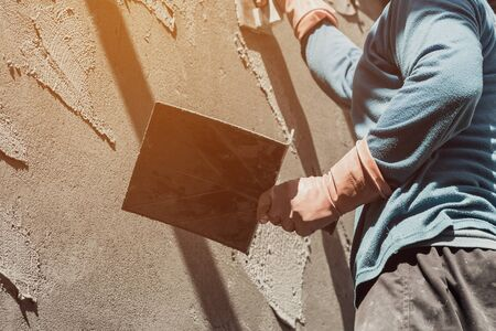 plasterer: plasterer concrete worker at wall of home construction building