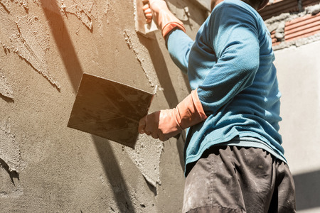 plasterer: plasterer concrete worker at wall of house construction