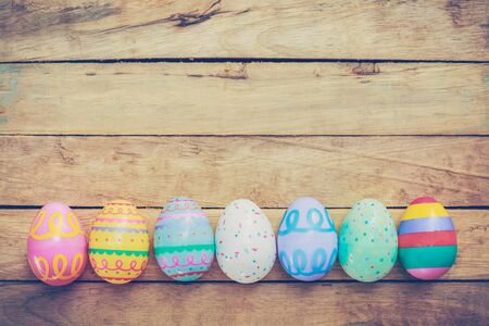 fun background: Easter eggs on wooden background with vintage tone.