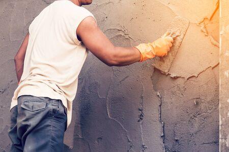 plasterer: man plasterer concrete working at wall of home construction building.