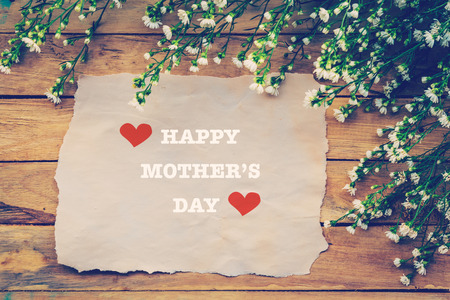 agradecimiento: Happy Mothers day on brown paper with white flower on wooden board Foto de archivo