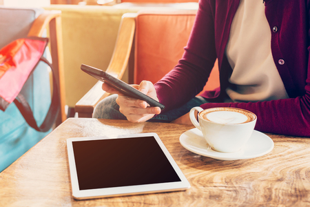 Woman using mobile phone in cafe. Female with tablet and coffee.