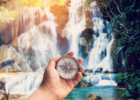 distractions: Hand man holding compass at Kuang Si waterfalls in Luang Prabang, Laos. Stock Photo
