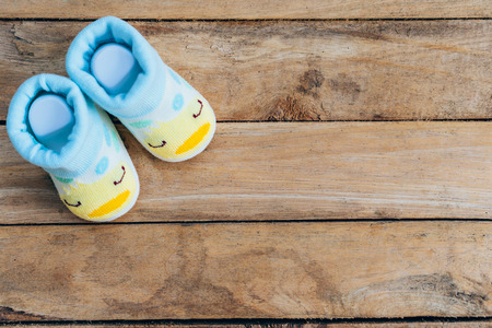 baby isolated: Baby shoes on wooden background with space